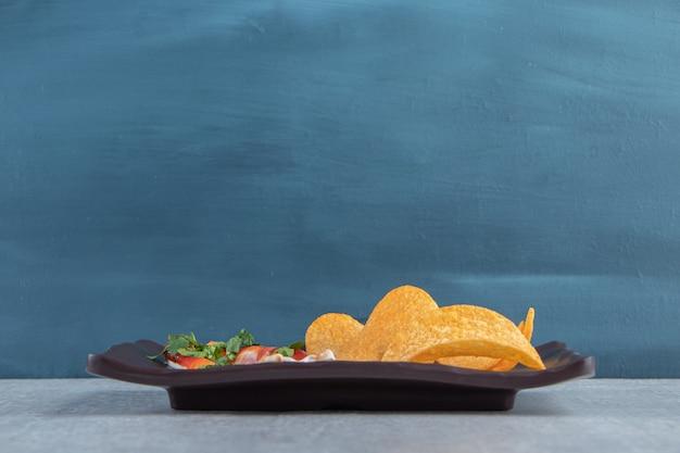 Хрустящие чипсы вместе с кетчупом и майонезом на темной тарелке.