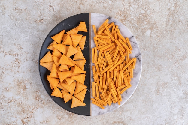 Хрустящие чипсы и гренки на тарелке, на мраморе.
