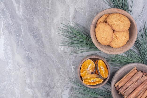 Хрустящее печенье в деревянной чашке с палочками корицы и сухими дольками апельсина вокруг.
