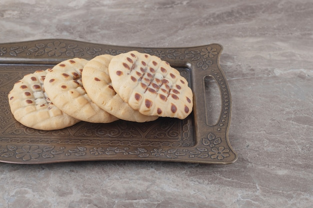 Crispy cookies on an ornate tray on marble