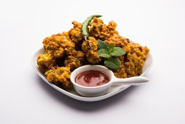 Хрустящая кукуруза пакора или пакода, бхаджи, бхаджи, баджи или паттиче. подается с томатным кетчупом