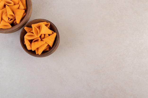ベージュのテーブルに置かれたボウルのクリスピーコーンスナック。
