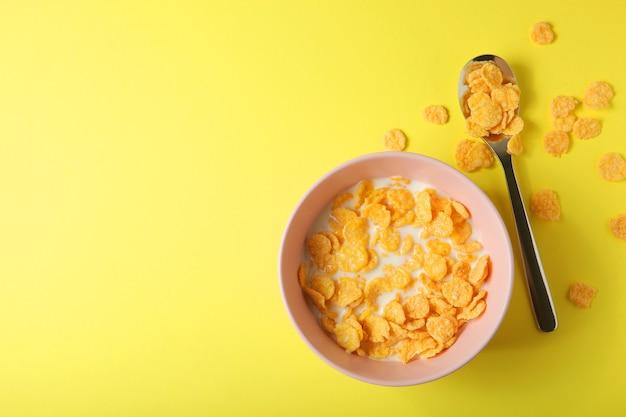 색깔 있는 배경 클로즈업에서 아침 식사로 우유를 곁들인 바삭한 콘플레이크 프리미엄 사진
