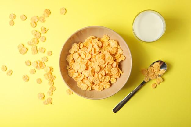 색깔 있는 배경 클로즈업에서 아침 식사로 우유를 곁들인 바삭한 콘플레이크