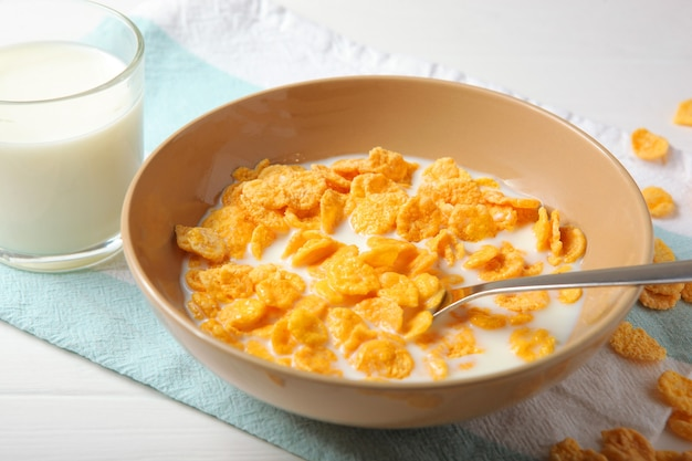 テーブルのクローズアップで朝食にミルクとクリスピーコーンフレーク