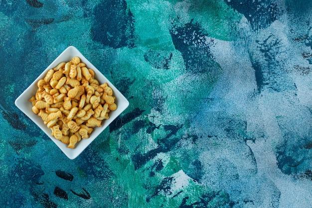 Хрустящая рыба-крекер в миске на синем столе.