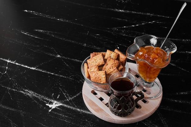 Хрустящие крекеры в стеклянной чашке на черной поверхности со стаканом чая и конфитюром.
