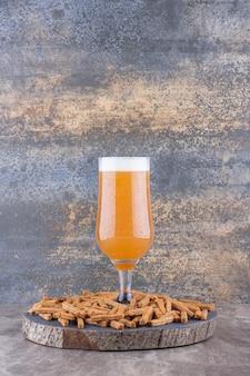 Хрустящие крекеры с пивом на дереве. фото высокого качества