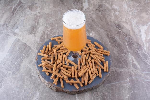 木片にビールを添えたサクサクのクラッカー。高品質の写真
