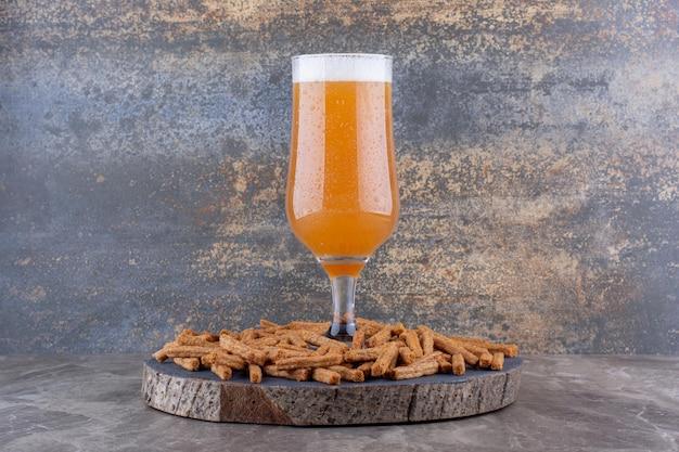 Cracker croccanti con birra sul pezzo di legno