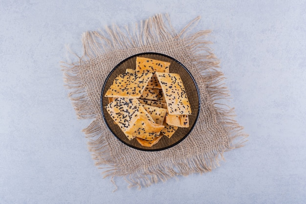 Crispy crackers with black seeds in dark glass bowl.