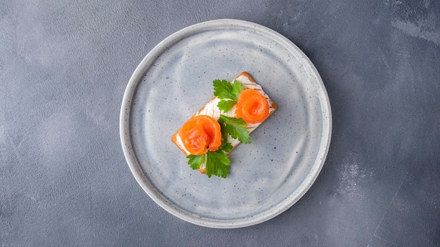 サーモンと豆腐チーズをプレートに乗せたサクサクのクラッカー。朝食のコンセプト。上面図。