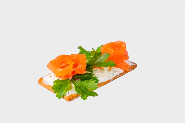Crispy crackers with salmon and curd cheese isolated on white