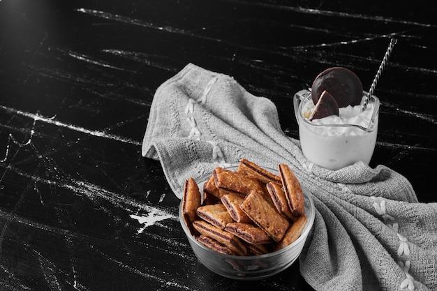 アイスクリームのカップを脇に置いたガラスカップのサクサクしたひび割れ。