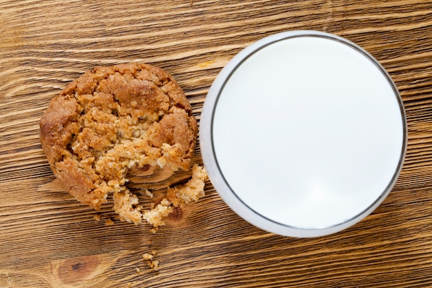 나무 테이블에 바삭 바삭한 밀 쿠키, 근접 음식, 생과자에 더 나은 맛을주는 흰 우유 한잔