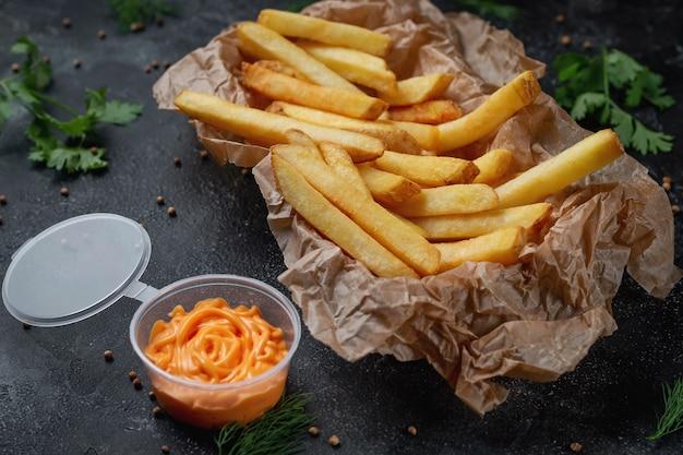 Хрустящий вкусный картофель фри на темном каменном фоне с сырным соусом. ресторан быстрого питания. здоровый вариант быстрого питания. жаренная картошка