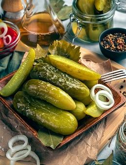 Хрустящие, вкусные маринованные огурцы крупным планом, лук, специи, масло на сером фоне. кулинарный фон, вертикальный вид.