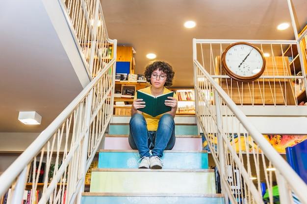 Crispy female reading book sitting on steps.