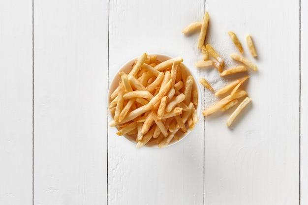 흰색 나무 테이블에 그릇에 바삭한 감자 튀김