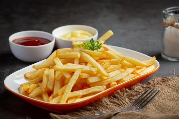Patatine fritte croccanti con ketchup e maionese.