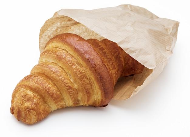 サクサクのフレッシュバタークロワッサン。紙袋に入っています。白い背景で隔離。