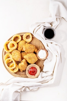 Crispy fried breaded chicken fillet with fried onion rings and potatoes served with sauce over white texture background. top view, flat lay. copy space