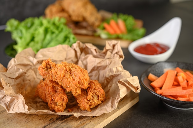 Crispy fried chicken on a cutting board with tomato sauce and carrot