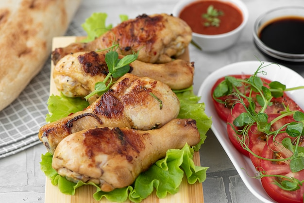 Хрустящие жареные куриные ножки со свежими помидорами и листьями салата