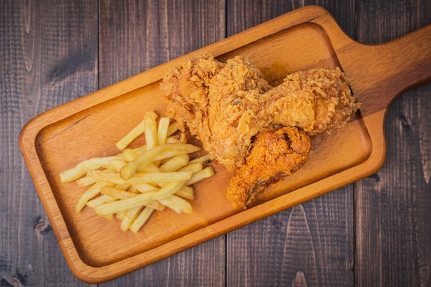 Crispy fried chicken and french fries potatoes on wood plate