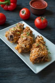 Хрустящие жареные куриные ножки в панировке с картофелем фри. запеченные голени украшены овощами и зеленью. быстрое питание. неправильная еда. темный деревянный стол.