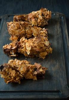 チップスでパン粉をまぶしたカリカリのフライドチキンの脚。ファストフード。間違った食べ物。暗い背景の木。