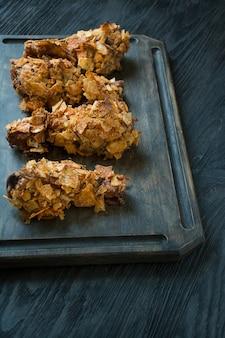 Хрустящие жареные куриные ножки в панировке с картофелем фри. быстрое питание. неправильная еда. темный деревянный стол.