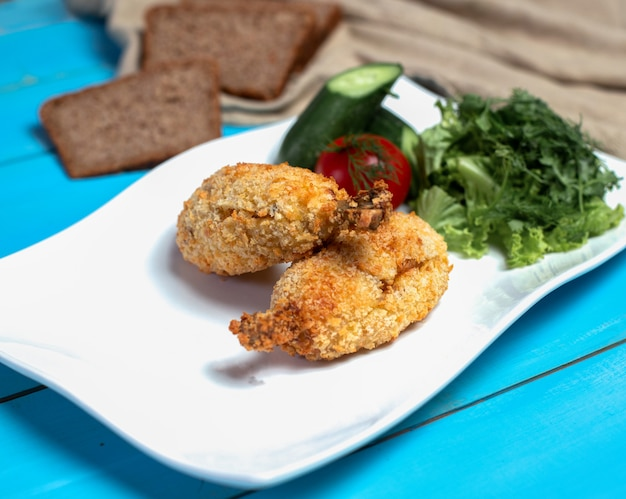 Crispy fried chicken legs with green salad.