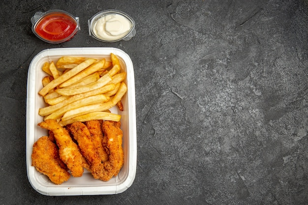 Pasto di pollo fritto croccante con patate servito con maionese ketchup sul tavolo scuro