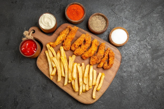 Crispy and fried chicken meal on wooden cutting board served with differen spices on dark table