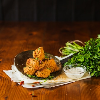 Crispy fried chicken nuggets on an old skimmer with garlic dip and fresh coriander