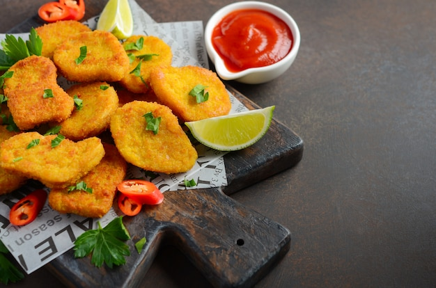 Crispy fried chicken nuggets with tomato sauce on dark background