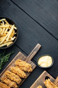 검은 나무 테이블에 바삭한 프라이드 치킨 부품