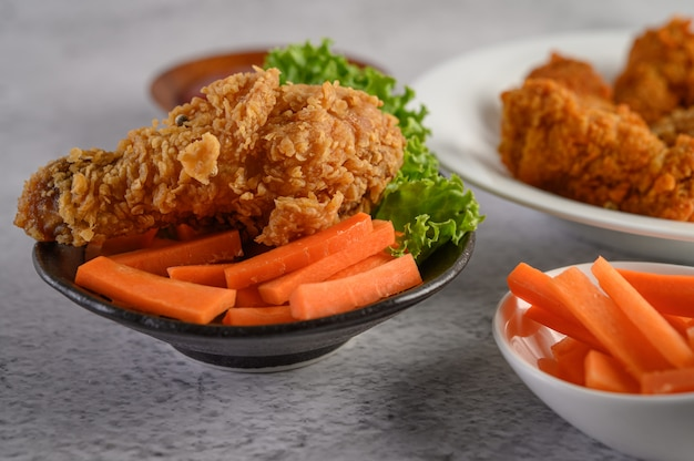 Crispy fried chicken on a plate with salad and carrot