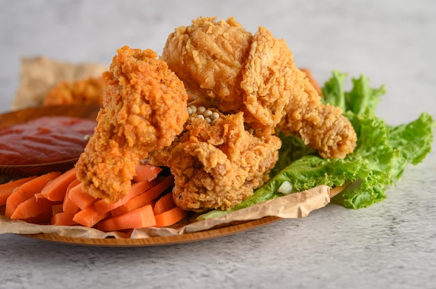Crispy fried chicken on a plate with tomato sauce and carrot