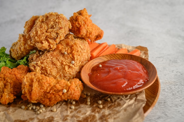 Crispy fried chicken on a plate with tomato sauce