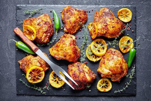 Хрустящие жареные куриные бедра с обжаренными ломтиками лимона и тимьяном на черной каменной доске на бетонном столе, вид сверху, плоский, крупный план