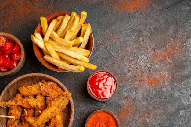 Хрустящий жареный цыпленок с нарезанными помидорами кетчупом и перцем на смешанном цвете