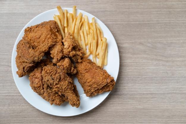 나무 테이블에 흰 접시에 감자 튀김과 바삭한 프라이드 치킨.