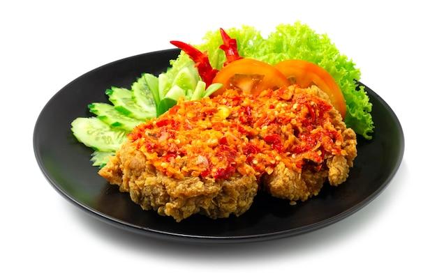 흰색 배경에 고립 된 검은 접시에 뜨겁고 매운 소스와 바삭한 프라이드 치킨