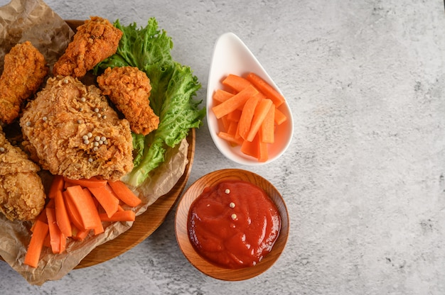 Crispy fried chicken on a wooden plate with tomato sauce and carrot