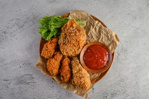Crispy fried chicken on a wooden plate with tomato sauce