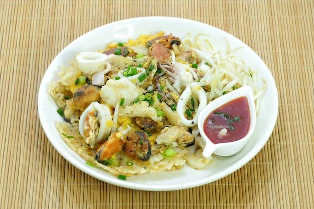 カリカリに揚げたアサリのムール貝と卵のパンケーキ。あさりムール貝のオムレツ。タイの屋台の食べ物(卵入りクリスピーパンフライドムール貝)