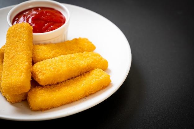 ケチャップを添えたパン粉を添えたサクサクの揚げ魚の指