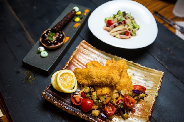 Crispy fried fish served with fried aubergine and fresh tomato salad